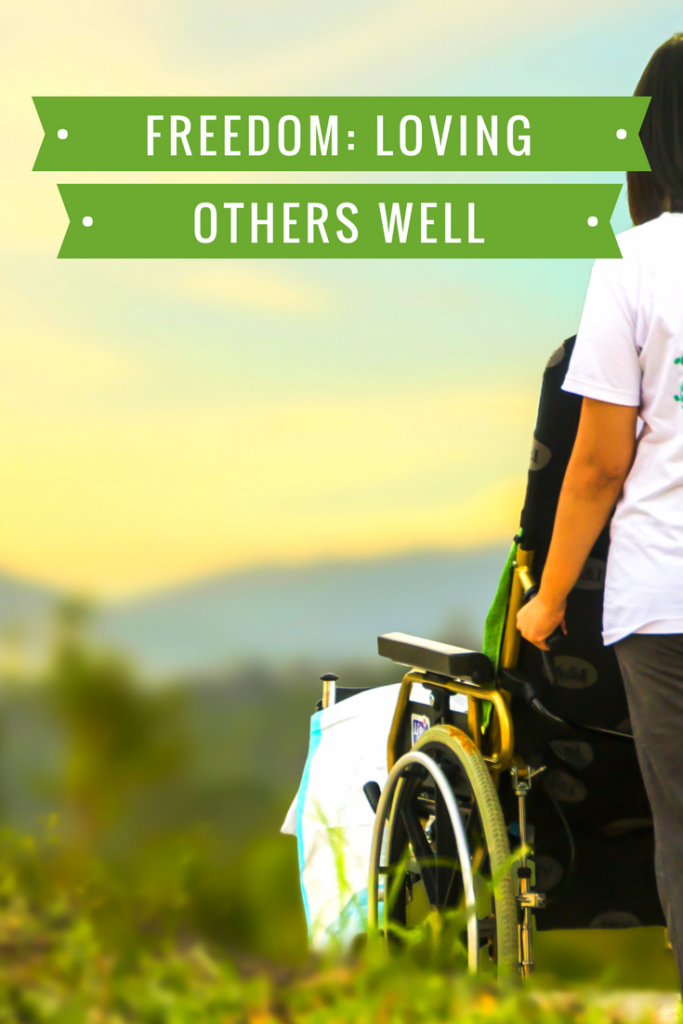 Truth - Freedom: Loving others well. Image - individual pushing someone in a wheelchair